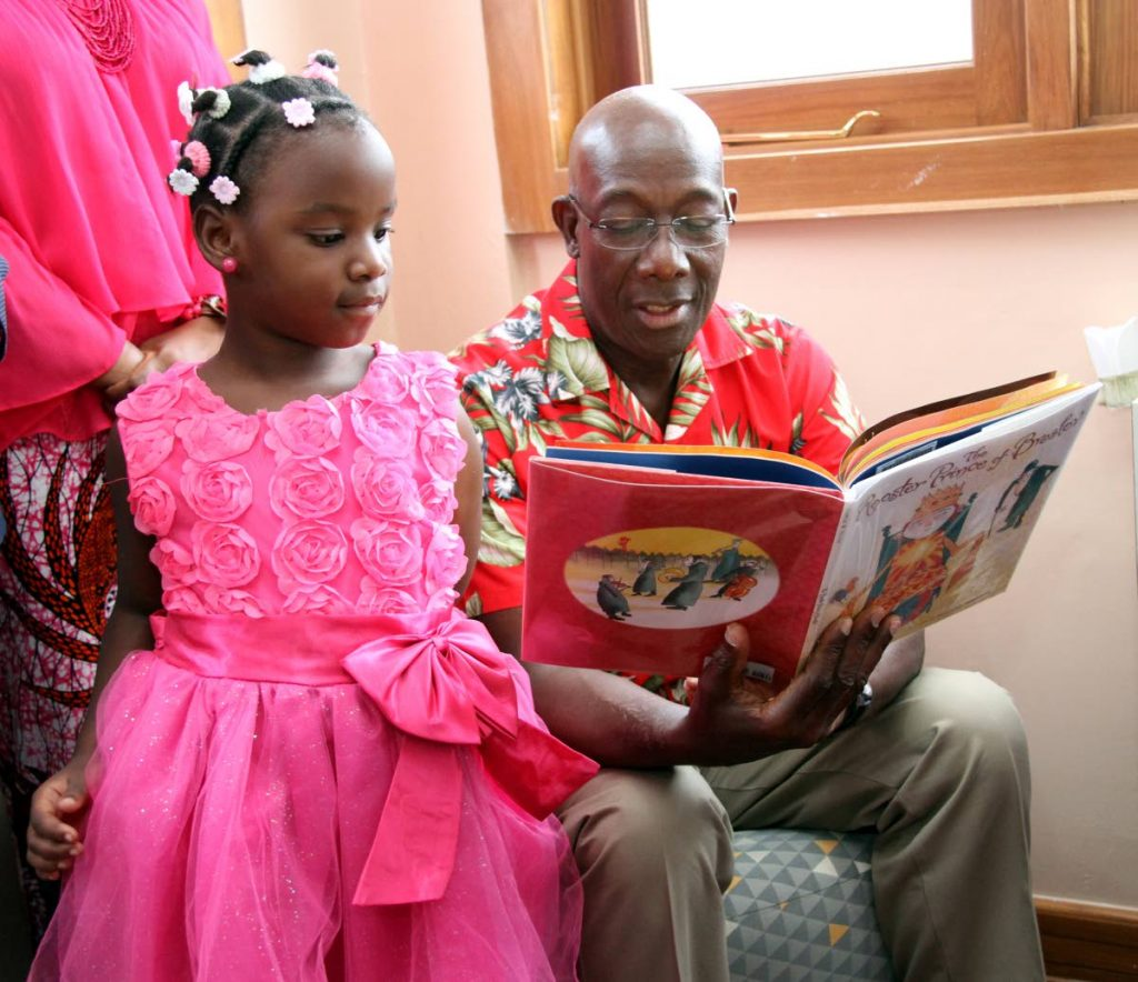 Anaya Moses listens as Prime Minister Dr Keith Rowley reads The Rooster Prince of Breslov to her at the opening of the Carenage Homework Centre and Police Youth Club on March 10, 2018. PHOTO BY SUREASH CHOLAI