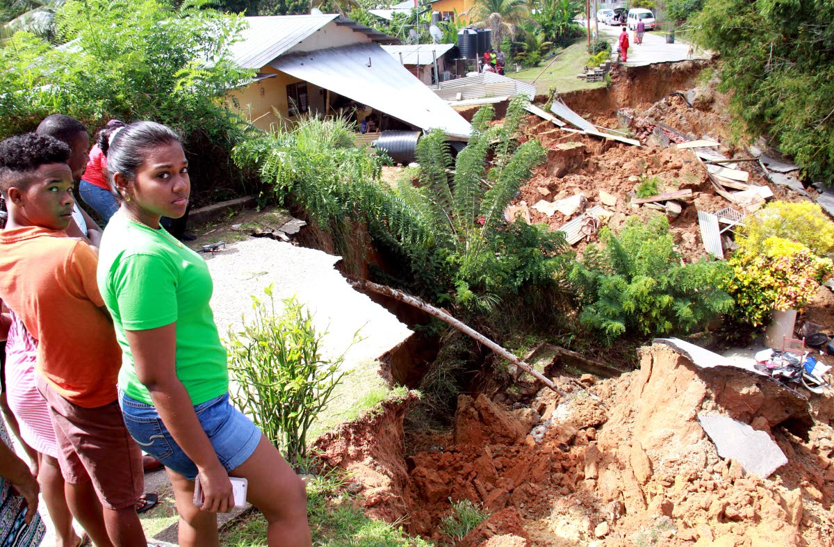 COLLPASE: Residents stand near the area in Bamboo Village, Cedros where a sink hole on Monday  caused a house to and sections of the roadway to collapse.