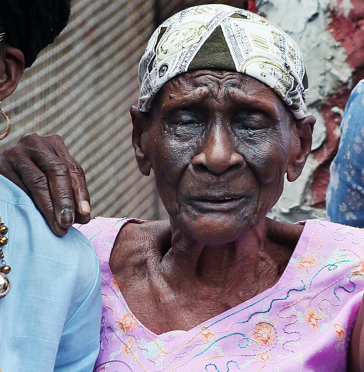 SORROW: Geraldine Baptiste, 94, weeps for James when his body was brought to her home for a final viewing.