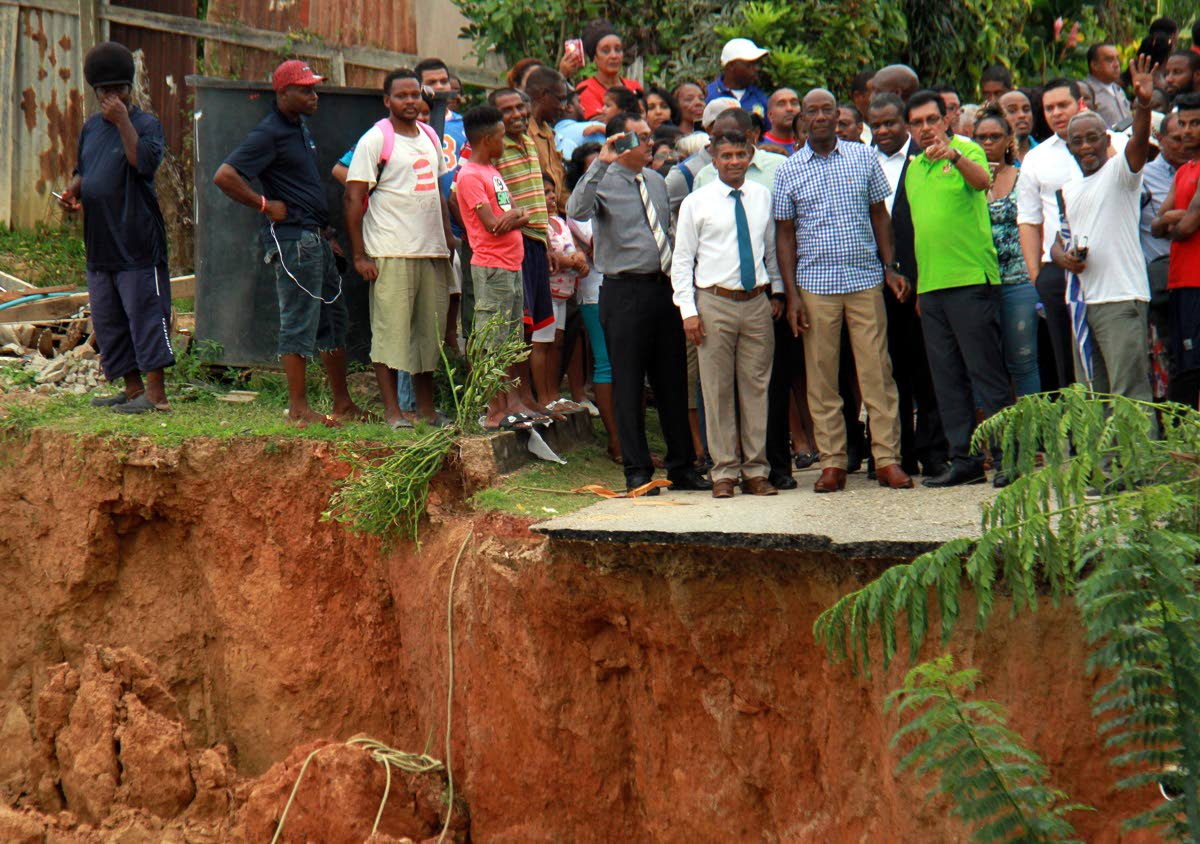 ON THE EDGE: Prime Minister Dr Keith Rowley (in plaid shirt) surveys the damage yesterday in Bamboo Village, Cedros.