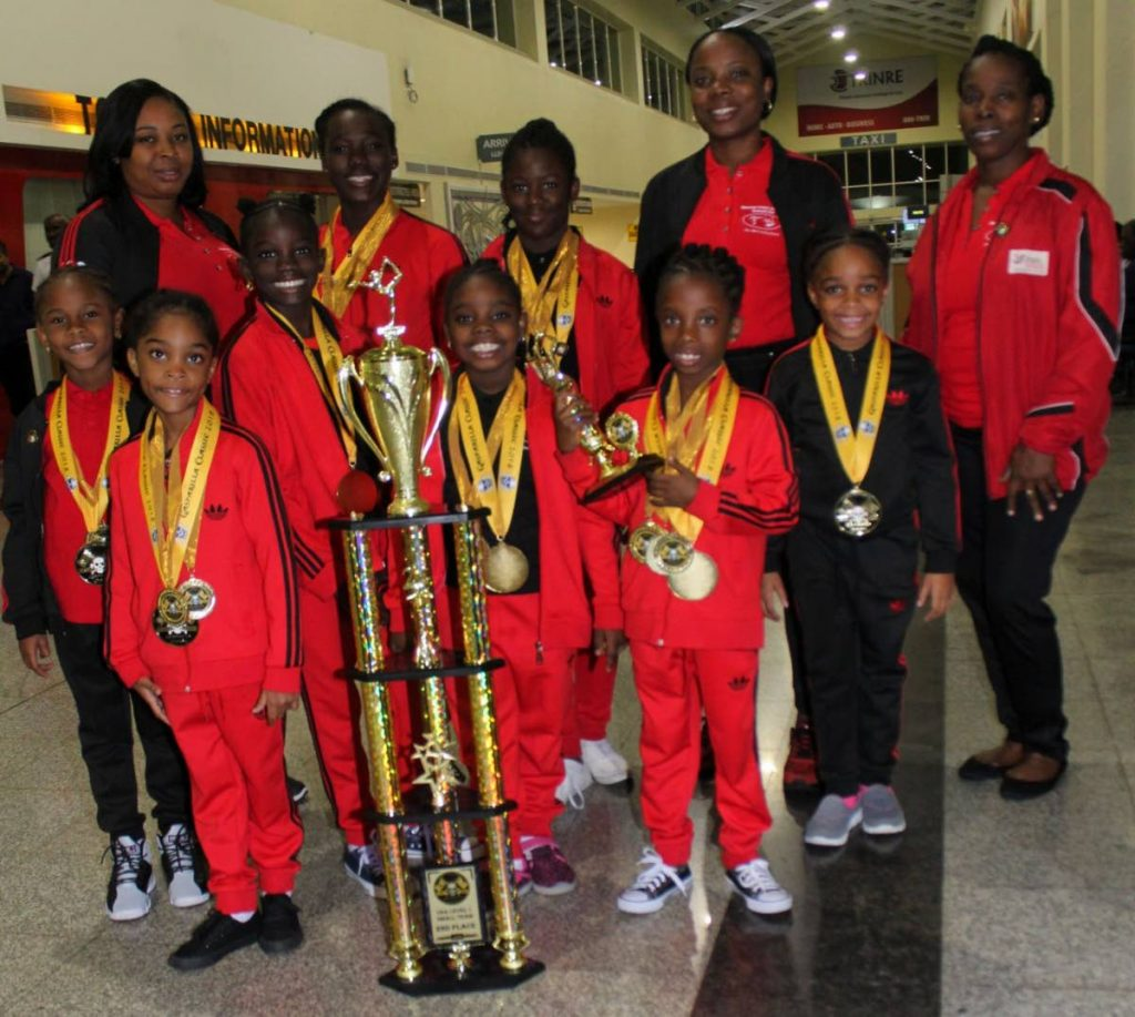 Mucurapo Gymnastics Achievers Club athletes and coaches show off their trophies and medals won last week in Florida.