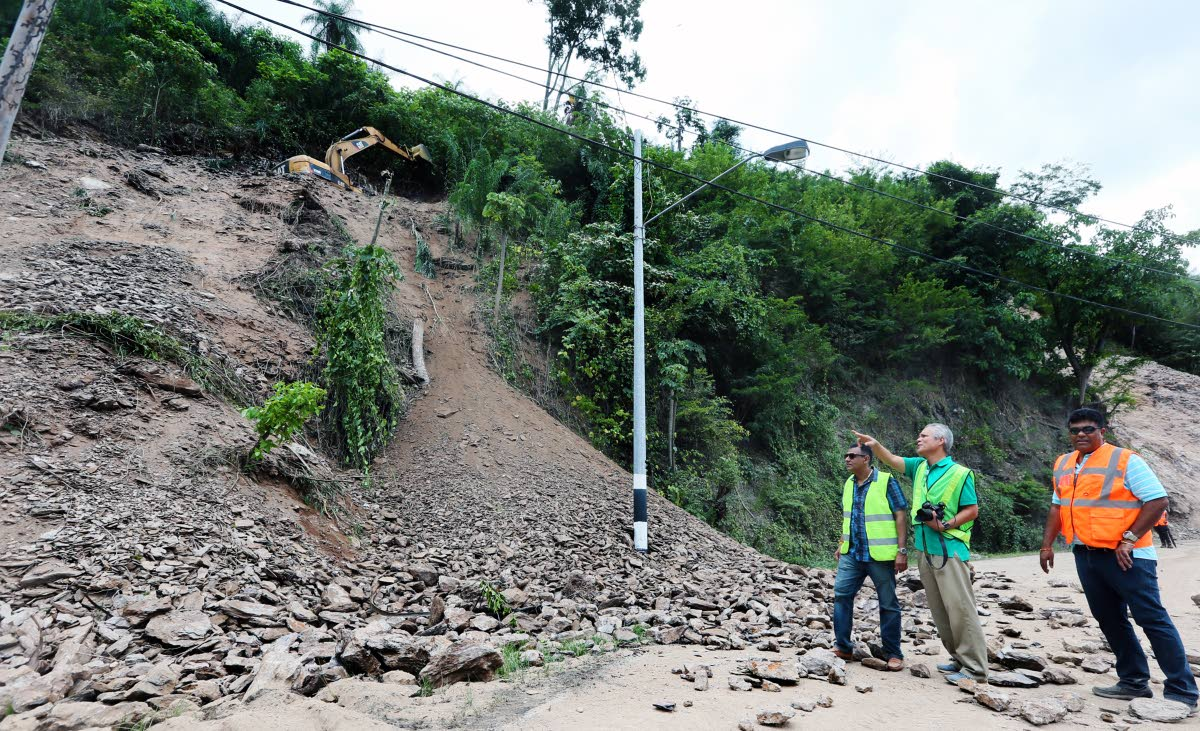 Major works: Minister of Works and Transport Rohan Sinanan, left to right, engineer Dr Derek Gay and acting Director of Highways Navin Ramsingh, look on as an escavator works on a ridge along Lady Young Road yesterday. The road is due to reopen on Monday after a landslip this week. PHOTO BY AZLAN MOHAMMED