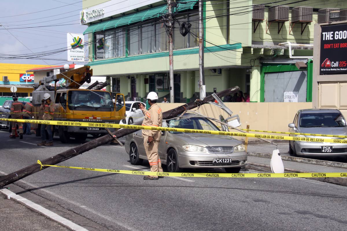 CRASH SCENE: Hollis Avenue in Arima had to be cordoned off for several minutes yesterday after a rotting utility pole fell on this car.