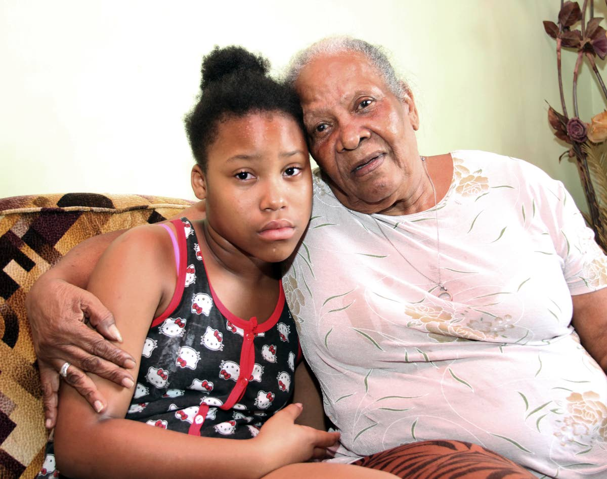 Grandmom Ida Armstrong consoles Kelis Armstrong the daughter of Melissa Tricia Emananuel ,the woman who was killed on Friday night inside a taxi during a robbery on Wrightson  Road , Port of Spain  .( at her home on Mt Pleasant Road Arima)