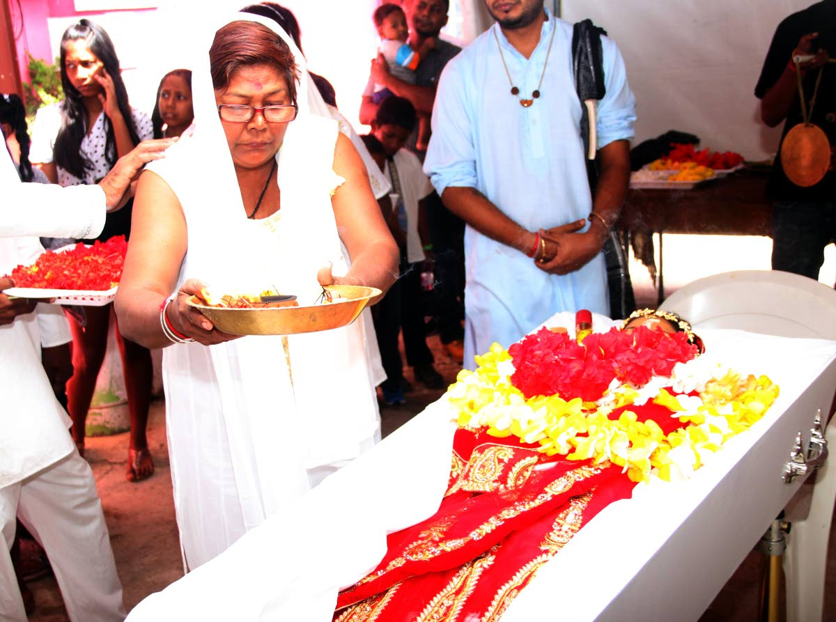 FOR MY DAUGHTER: Deomattee Madoo performs a Hindu ritual over her daughter Rachel Madoo's body at her funeral yesterday at the family's home in Chaguanas.