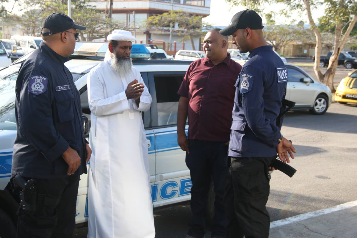 DEFENDING THE POLICE: Islamic Front  Leader Umar Abdullah speaks with police officers at the rally in Marabella on Sunday after accusing other Muslim groups of antagonising the police.     PHOTO BY ANSEL JEBODH