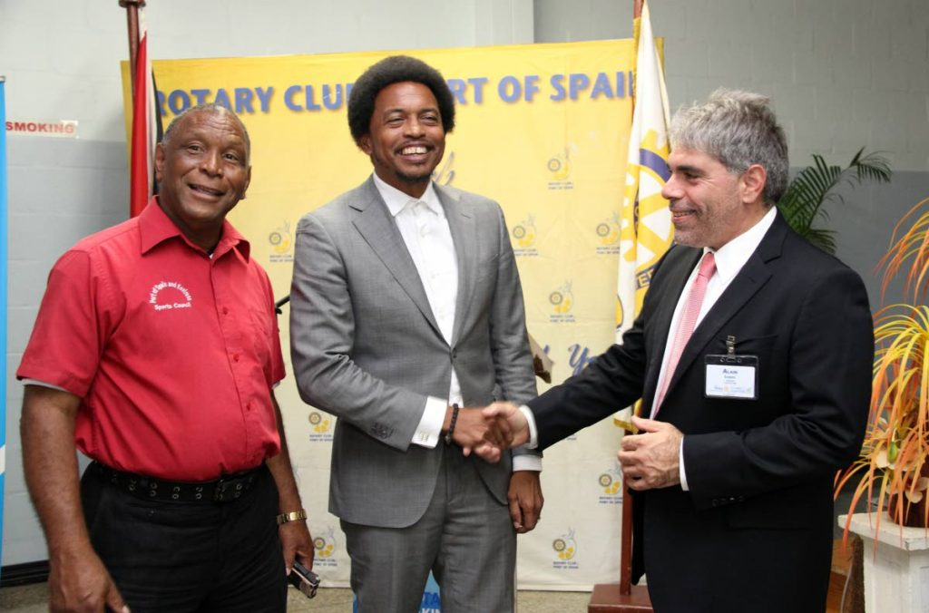 TTOC president Brain Lewis,centre, shakes hands, at the launch of the PoS District Games, with Alain Laquis, president of the PoS Rotary Club, while Kelvin Nancoo,organiser of the District Games looks on. The launch was held at the PoS Rotray Club office,Woodbrook.