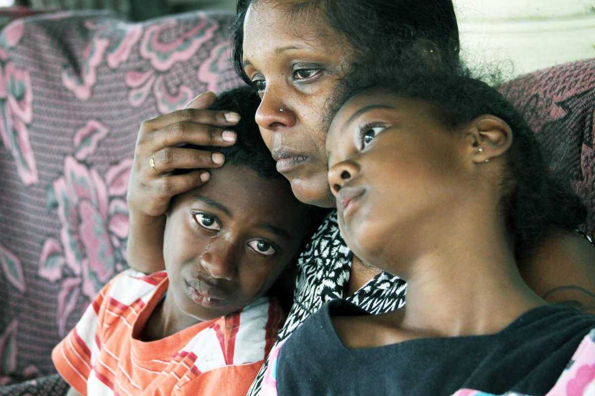 TEARS AFTER MURDER: Radica Pooran comforts her son Kayron and daughter Kyley yesterday at their Gasparillo home a day after the children's father and Radica's common-law husband Sgt Ken Palmer was shot dead during an altercation with a group of men. See Page 11A.PHOTO BY JEFF K MAYERS