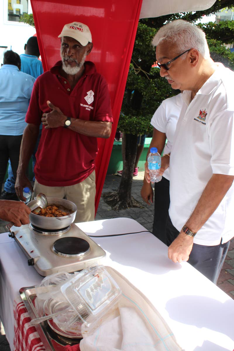 What's cooking?: Health Minister Terrence Deyalsingh takes careful note of a dish being cooked at the NWRHA Care Fair, San Juan Promenade, Croisee yesterday. PHOTO BY ENRIQUE ASSOON