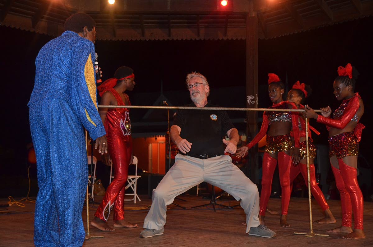 A participant in the Governor General's Cup (GGC) Caribbean Air Rally enjoy the limbo at a reception hosted by the Division of Tourism at the Pembroke Heritage Park last Friday.