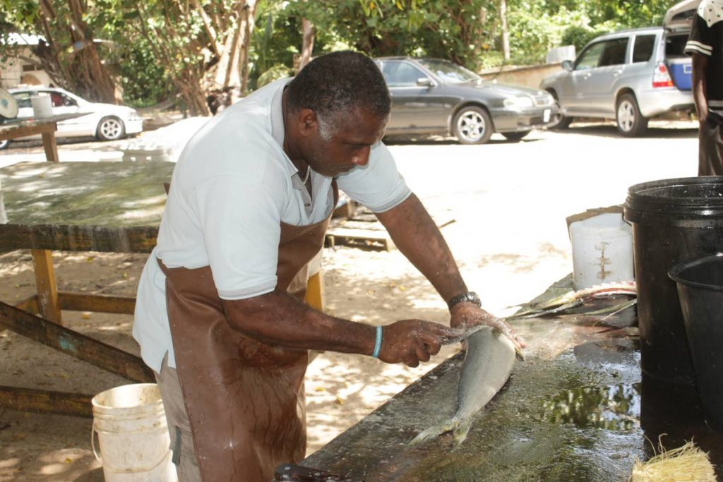 A Pigeon Point fisherman cleans fish for sales to residents