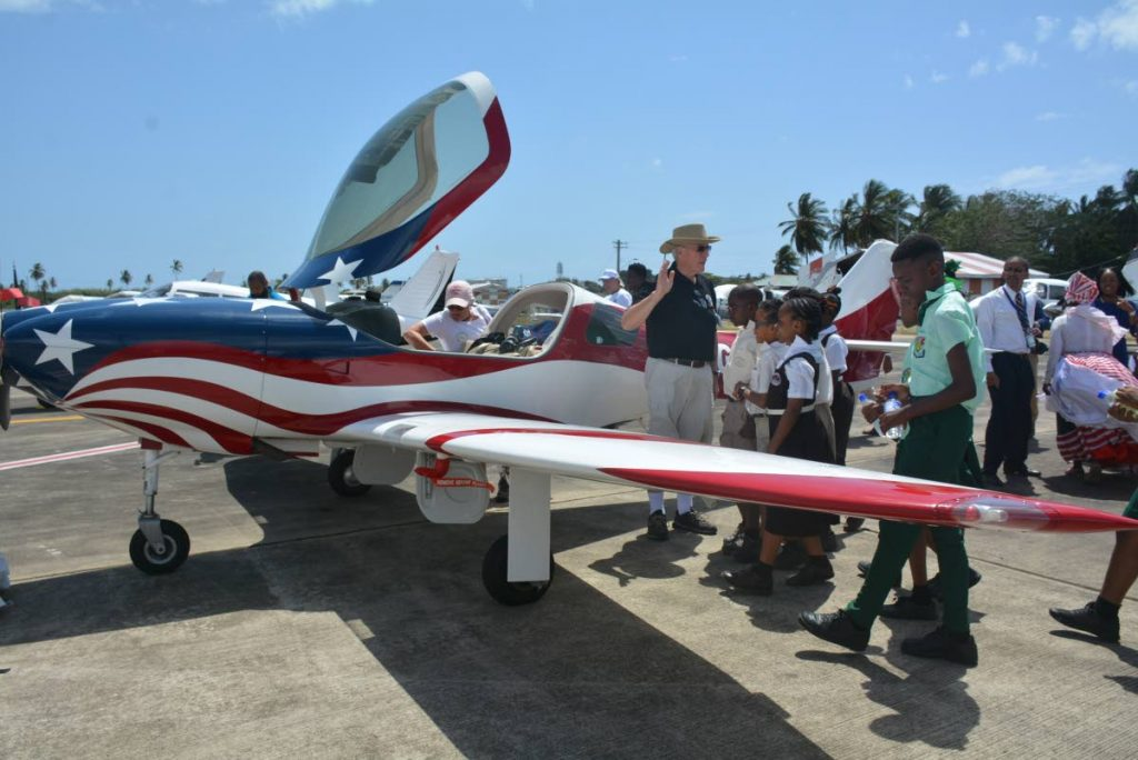 Pilot Richard Schmidt gives primary school students a tour of the aircraft which landed at the ANR Robinson Airport last Friday on a pilots' two-day training stop-over for Governor General's Cup Caribbean Air Rally 2018.