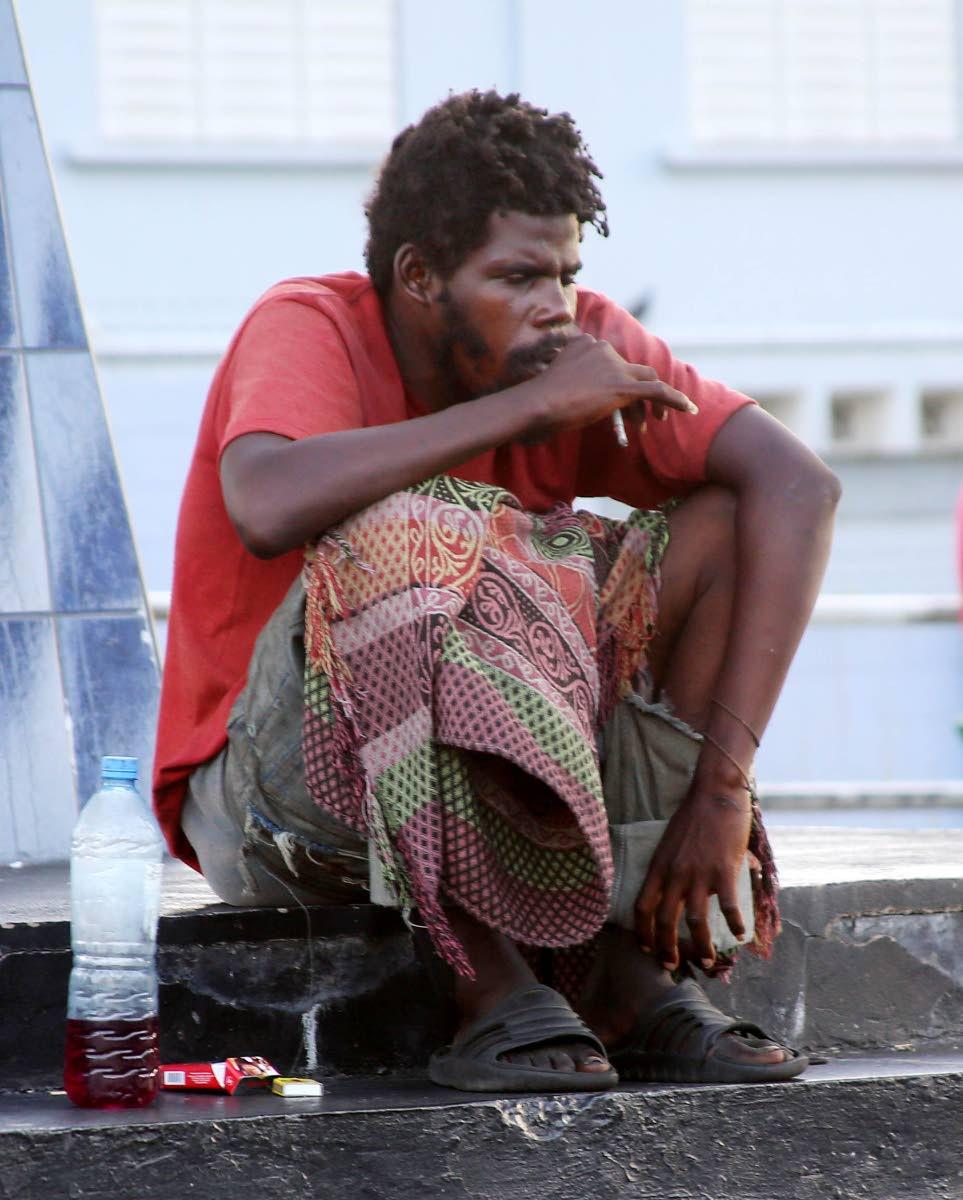 A homeless man sits on Marcus Gavey monument, Harris Promenade, San Fernando.