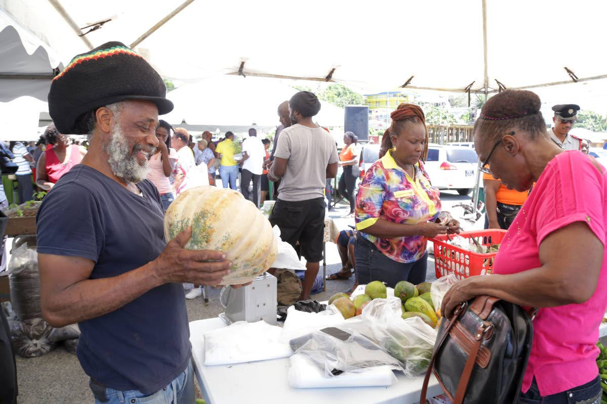 A farmer shows off a prized pumpkin to a visitor at World food Day celebrations on October 16, 2017 in Scarborough.