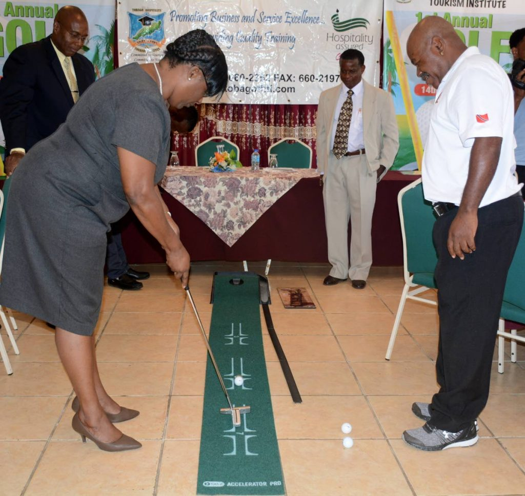 Administrator in the Division of Education, Jacqueline Job, tries her hand at a stroke as pro golfer Carlos Baynes looks on at the announcement of the Tobago Hospitality and Tourism Institute (THTI first Annual Golf Tournament on July 14-15 at the Magdalena Grand Beach and Golf Resort in Lowlands.