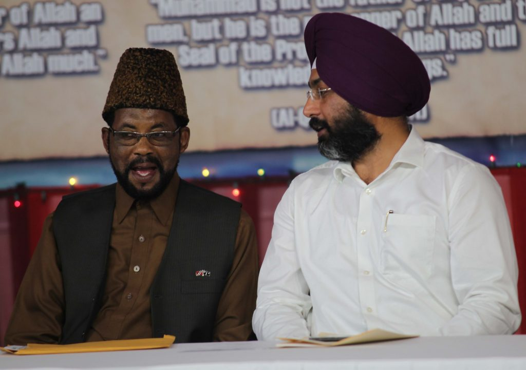 Maulana Ibrahim Bin Yaqub of the TT Ahmadiyya Muslim Community and Sukhjit Singh speak during a peace sumposium at the National Centre in Gran Couva yesterday. PHOTO BY LINCOLN HOLDER