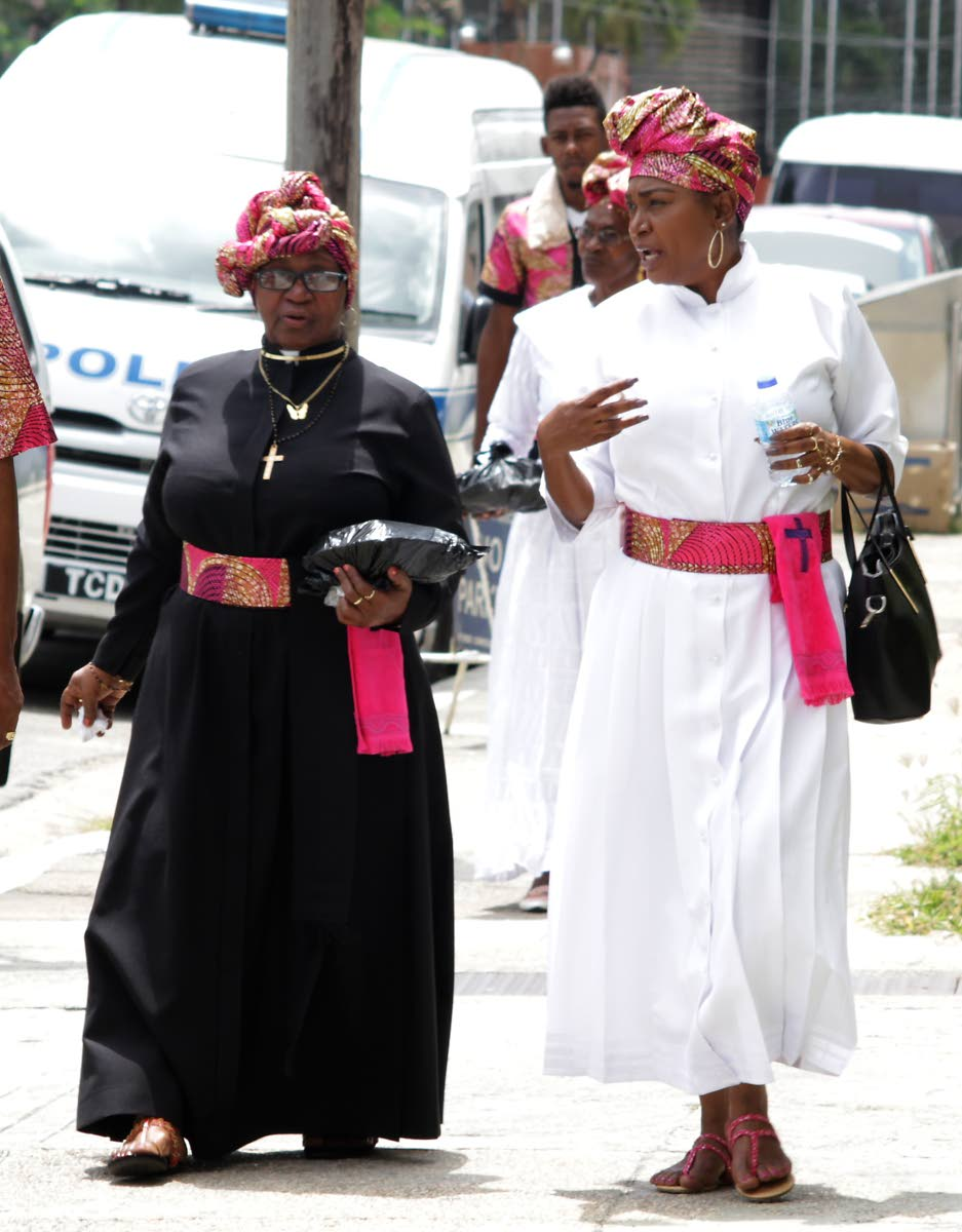 On the way: Two women chat on their way to the thanksgiving service for Spiritual Shouter Baptist Day at City Hall, Port of Spain on Friday.  PHOTO BY ROGER JACOB