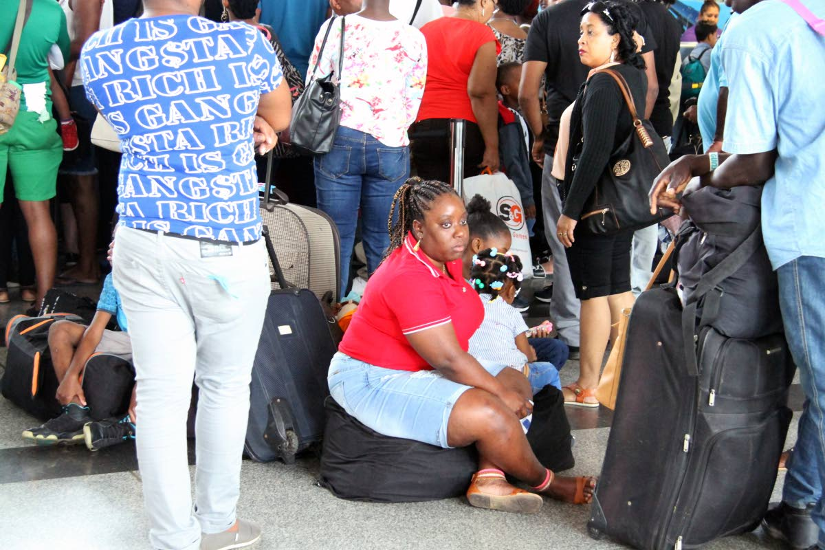 On the floor: A woman with children sit on their luggage among crowded lines as passengers checked in for flights to Tobago at Piarco International Airport yesterday. PHOTO BY SUREASH CHOLAI