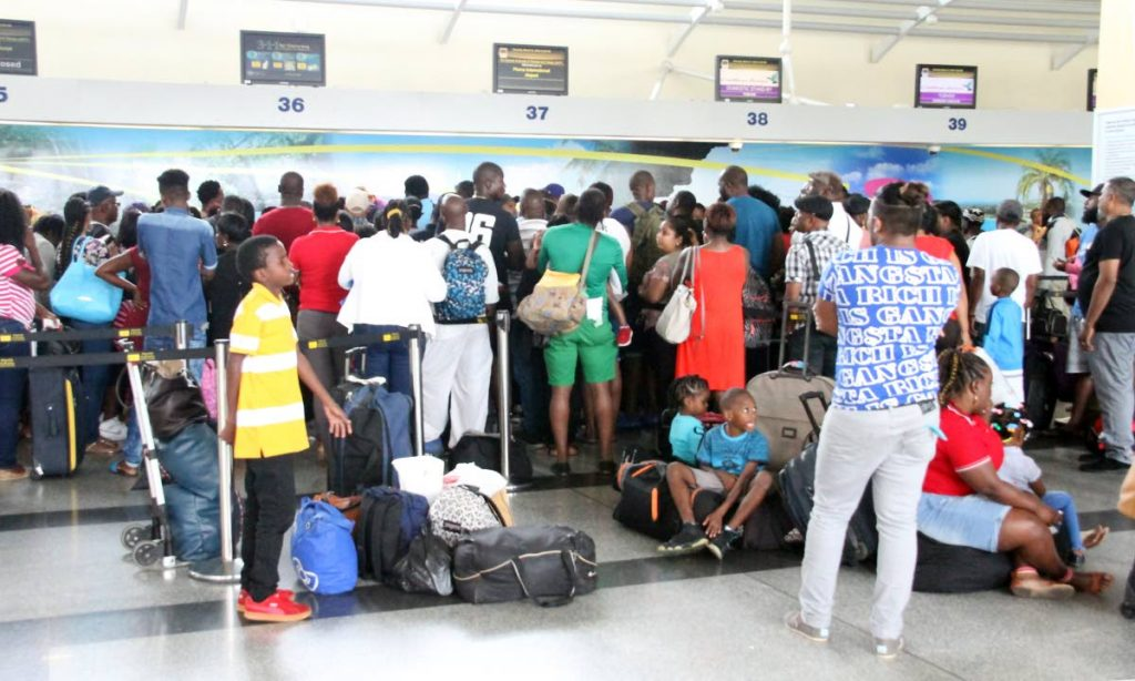 Waiting to fly: Passengers crowd the domestic counter for flights to Tobago, while others including children sit on luggage, at Piarco International Airport on March 31, over the Easter holiday weekend. CAL wet-leased Liat planes to help meet the demand on the airbridge. PHOTO BY SUREASH CHOLAI