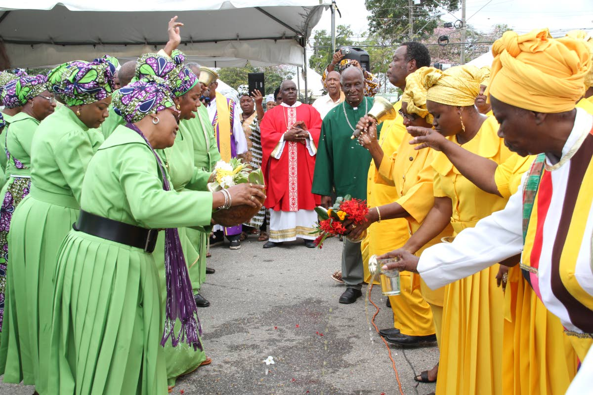 Blessings: Members of Spiritual Baptist churches greet each other with offerings of water and flowers at the the National Congress of Incorporated Bapatist Organisations of TT's Liberation Day celebrations at Eddie Hart Grounds, Tacarigua yesterday. PHOTOS BY SUREASH CHOLAI