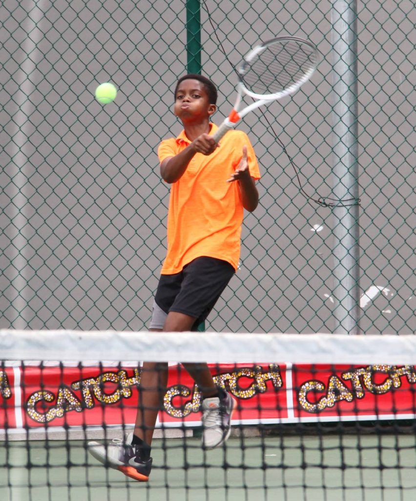 Andre Augustine makes a return to David Rodriguez yesterday at the National Racquet Centre, Tacarigua for the 30th Annual Catch National Juniour Tennis Championships.