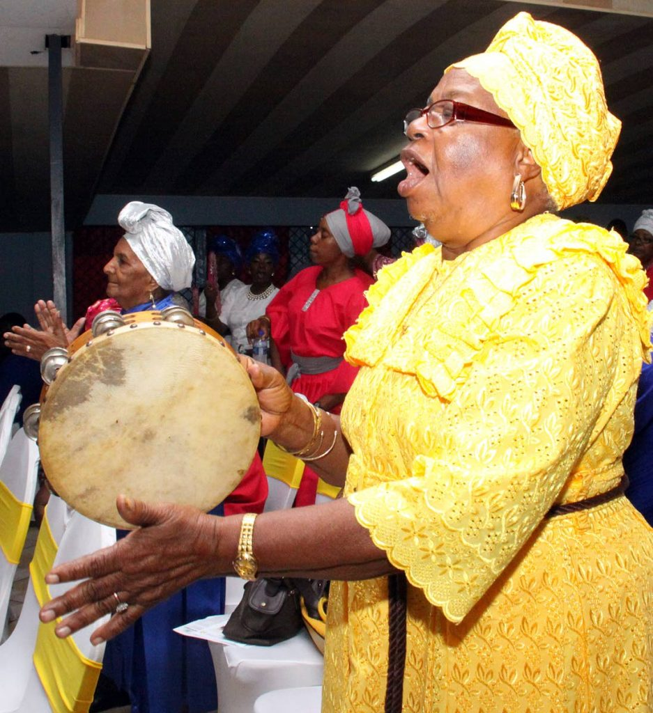 Rejoice!: A woman plays the tambourine during Spiritual Shouter Baptist Liberation Day celebrations at Maloney Empowerment Hall, Maloney yesterday. PHOTO BY ANGELO MARCELLE