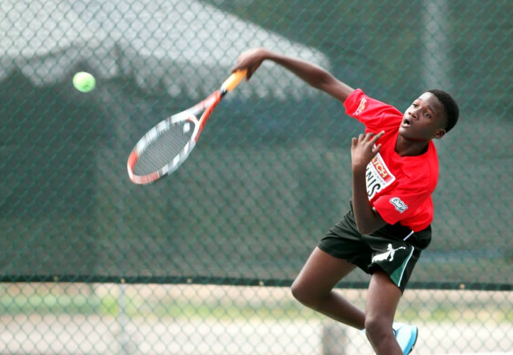Shae Millington returns to Etan Wong yesterday during a Boys Under-14 match at the National Racquet Centre, Tacarigua for the annual Catch national Juniour Tennis Championships. Photo by Sureash Cholai