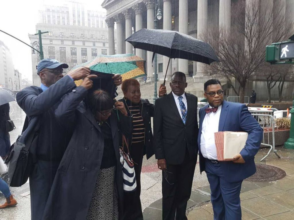 UNDER COVER: National Security Minister Edmund Dillon (second from right) is sheltered from the rain after leaving the New York Supreme Court yesterday.