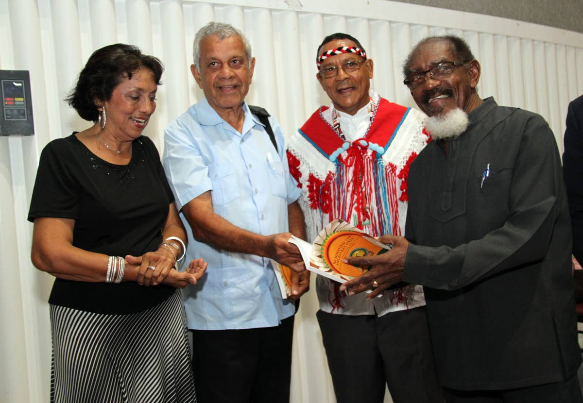 """BOOK FOR CHALKIE: First Peoples chief Ricardo Bharath Hernandez, 2nd from right, looks on as calypsonian Dr Hollis """"Chalkdust"""" Liverpool, right, holds a copy of the  book' Re-igniting the Ancestral Fires'. Also in photo from left are Jassie Singh and Dr Brinsley Samaroo. PHOTO BY SUREASH CHOLAI"""