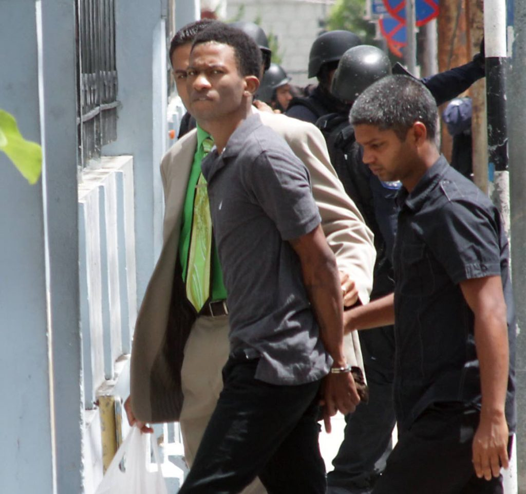 Andre Nicholas Lavia is escorted by police officers to the Port of Spain Magistrates' Court, where he appeared for the January 26 murder of prison officer Davendra Boodooram. Photo Roger Jacob