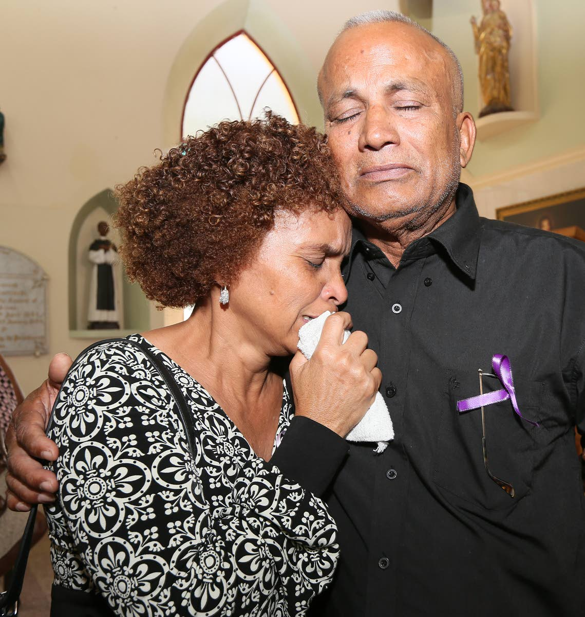 OUR GIRL IS GONE: Raphael Chuniesingh consoles his wife Fabiana yesterday at the funeral for their murdered daughter Christine at the Santa Rosa RC Church in Arima. PHOTO BY AZLAN MOHAMMED