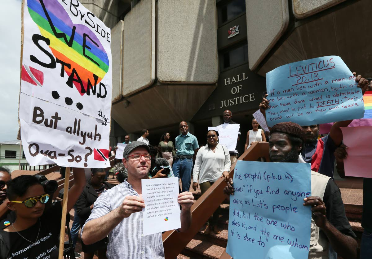 Opposing views: Members of the gay and Christian communities hold signs supporting their views on gay rights on the steps of the Hall of Justice, Port of Spain last Thursday, before Justice Devindra Rampersad's historic ruling that buggery laws were unconstitutional.  PHOTO BY AZLAN MOHAMMED