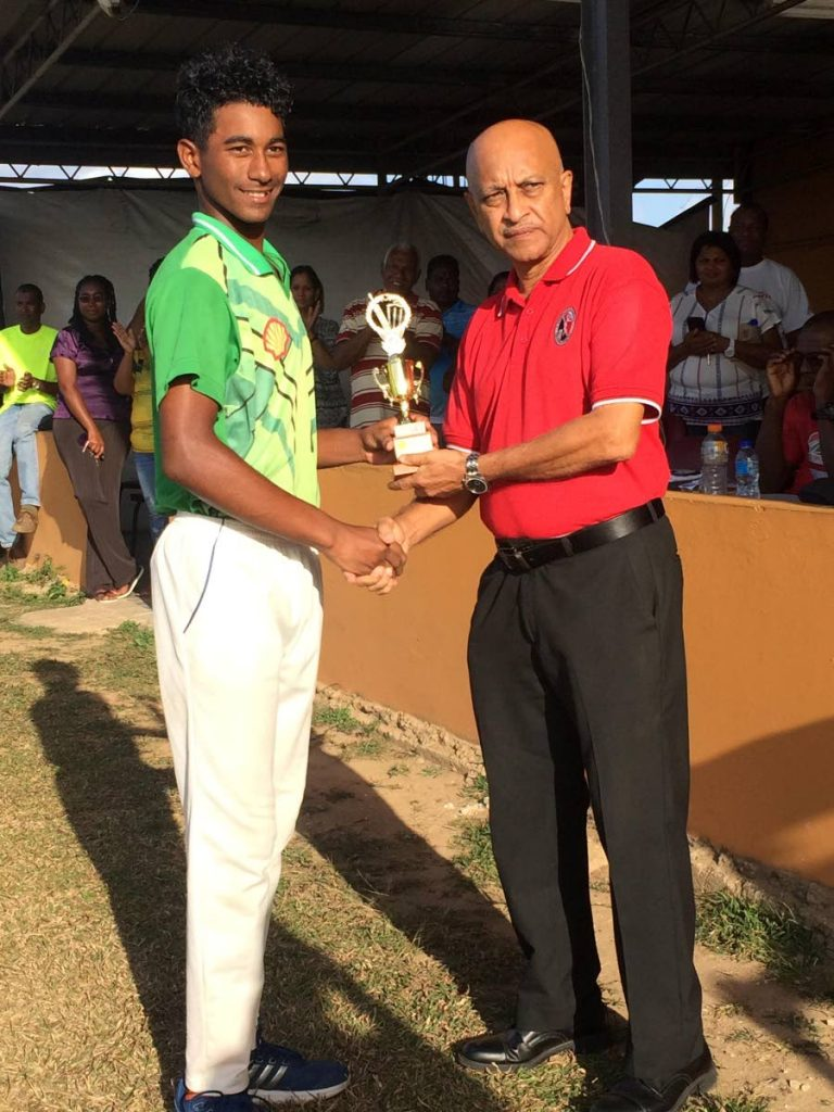 South's Antonio Gomez, left, receives his Man-of-the-Match award from TTCB official Dudnath Ramkessoon.
