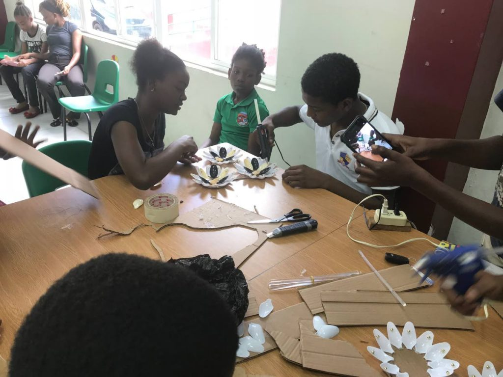 Youths learn how to create art from garbage in the Art From Trash initiative.