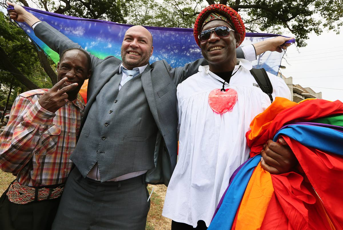 File photo: Gay rights activist Jason Jones celebrates at Woodford Square, Port of Spain with Kelvin Darlington (Saucy Pow), left, and another member of the LBGTQI community after the high court's ruling decriminalising gay sex.  PHOTO BY AZLAN MOHAMMED