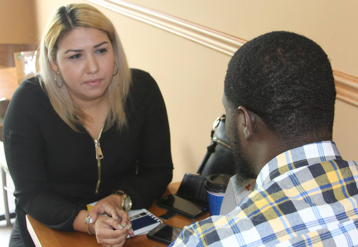 Greisy Gonzalez, left, speaks with Sunday Newsday's Jensen LaVende yesterday on the experiences of Venezuelans living in TT. PHOTO BY ENRIQUE ASSOON