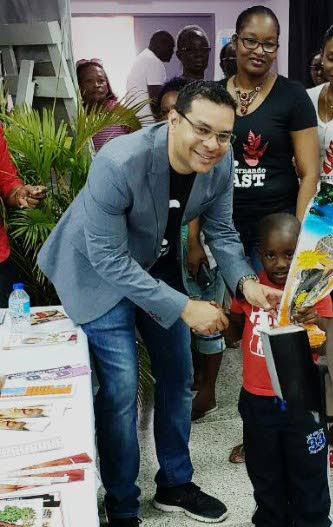 Tourism Minister Randall Mitchell greets a boy at yesterday's health fair held at the Pleasantville Community Centre.