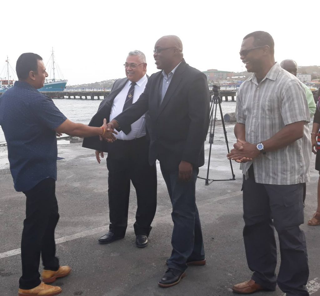 Minister of Works and Transport Rohan Sinanan greets  Tobago House of Assembly Chief Secretary Kelvin Charles as  Port Authority Board member Tommy Elias (centre) and an unidentified official look on after the arrival of the TT Spirit at the Scarborough port on Saturday.