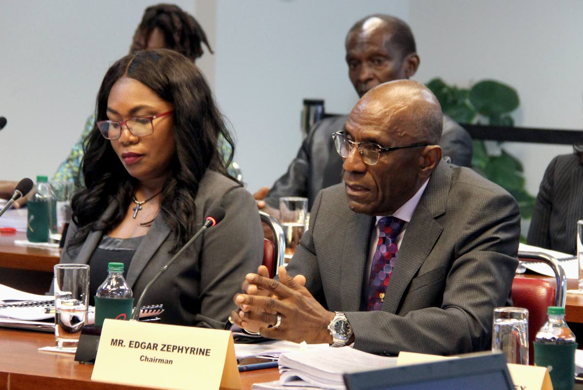 National Commission for Self-Help chairman Edgar Zephyrine responds to questions from the Public Accounts (Enterprises) Committee at the Parliament building yesterday.  With him is administrative head Janice Phillips.
