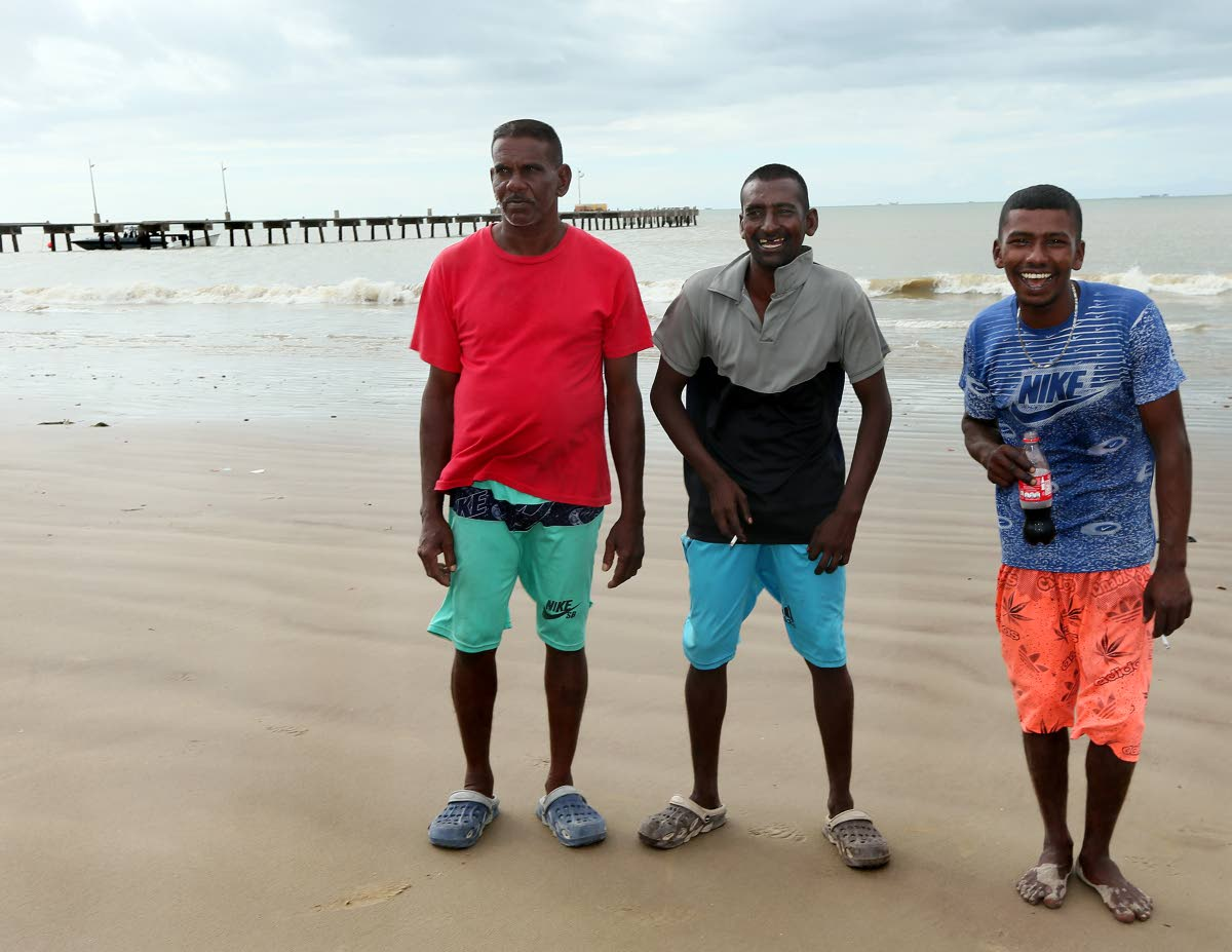 From Left Awarnath Hajarie, Nicholas Nanlal and Shammi Seepersad share a light moment on Cedros beach after being processed by local coast guard and Immigration officers yesterday. PHOTO BY AZLAN MOHAMMED