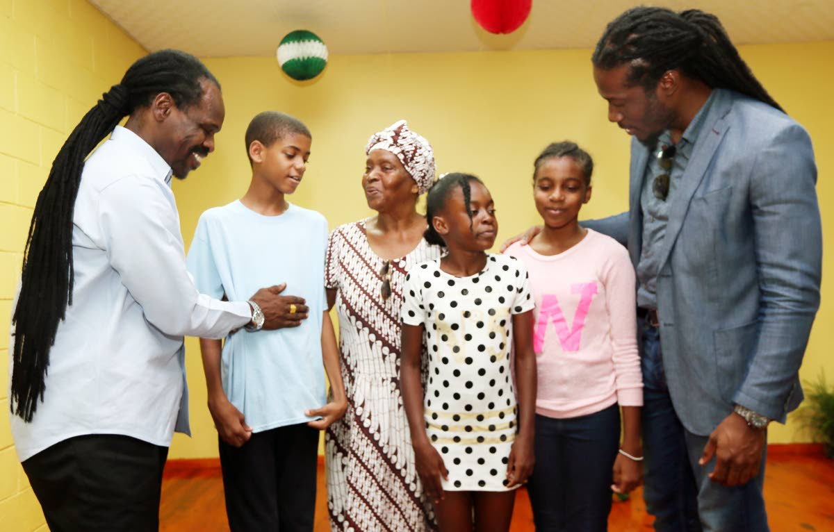PEP TALK: Minister in the Office of the AG Fitzgerald Hinds (left) gives some sound advice to SEA student Tyler Williams as Ena Garcia, who said a prayrer for the children looks on. At right, Laventille East/Morvant MP Adrian Leonce chats with Ruth Thompson and Maurina Mc Donald. PHOTO BY AZLAN MOHAMMED