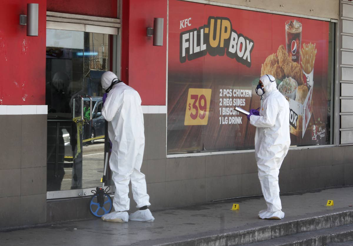 DEATH SCENE: Investigators process the area where a man was stabbed to death during a scuffle with a security guard at the Independence Square, Port of Spain branch of KFC yesterday.