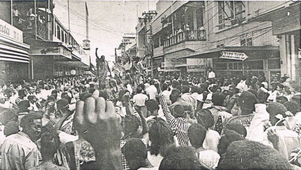 A newspaper clipping of scenes from the 1970 Black Power Revolution shows protesters swarming Frederick Street, Port of Spain.
