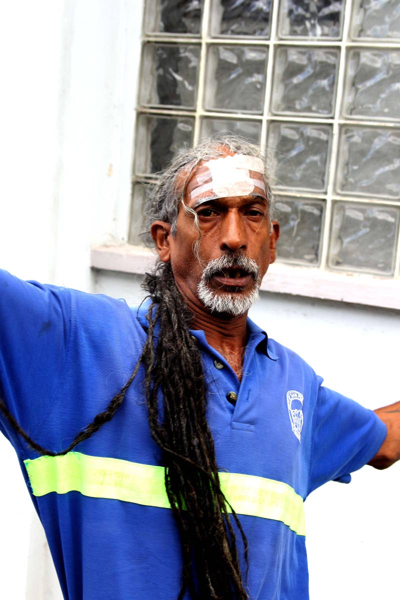 BUSS-HEAD:Dexter Oudit, whose head is heavily bandaged, leaves the San Fernando Magistrates Court yesterday after his son Joseph appeared charged with wounding him by allegedly  smashing a bottle on his forehead. PHOTO BY LINCOLN HOLDER