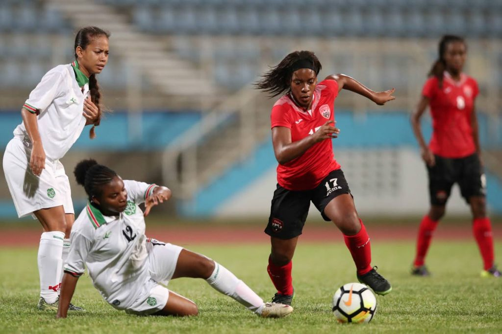 Trinidad and Tobago's Laurelle Theodore, right, skips past a challenge from Suriname's Abigail Breinburg in a CFU Women's Challenge Series match on Wednesday at the Ato Boldon Stadium, Couva.
