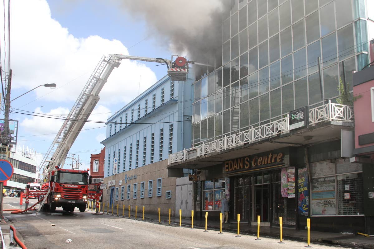 ON FIRE: Firemen use a hydraulic ladder to reach the top floor of the Edan's Centre to fight a fire in the Edan's Centre in San Fernando.