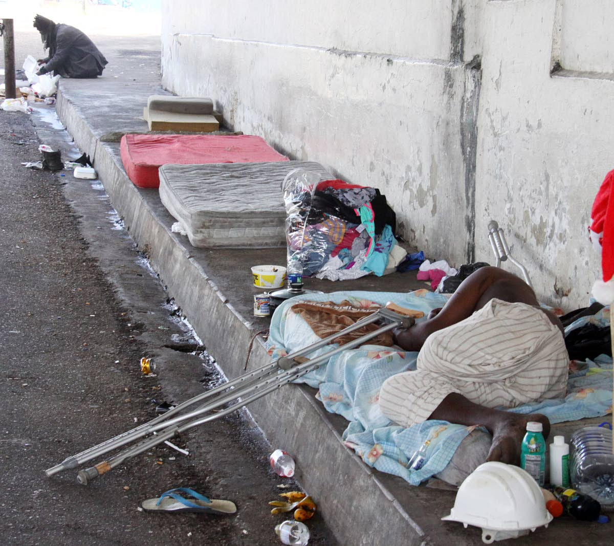 Homeless people on the ground floor of the Centre for Socially  Displaced People at Riverside Plaza in Port of Spain.