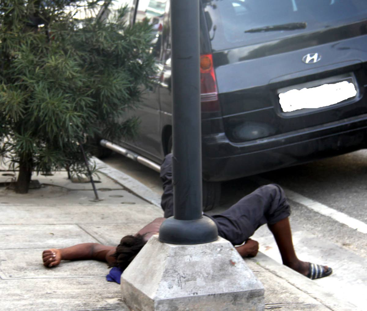 A street dweller sprawls on the pavement on St. Vincent Street Port of Spain.  PHOTO:ANGELO M. MARCELLE