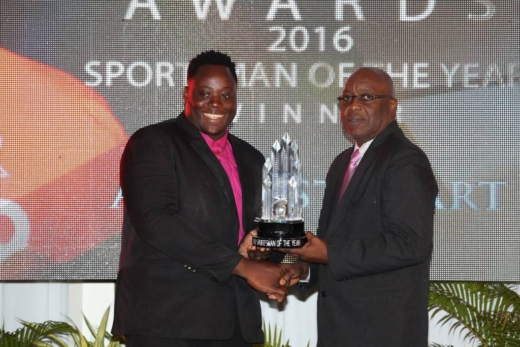 Para-Olympian Akeem Stewart, left, receives his trophy for THA Sportsman of the Year 2016, from Chief Secretary Kelvin Charles, at the THA Sports Awards held at the Magdalena Grand Beach and Golf Resort in Lowlands on May 20, 2017.