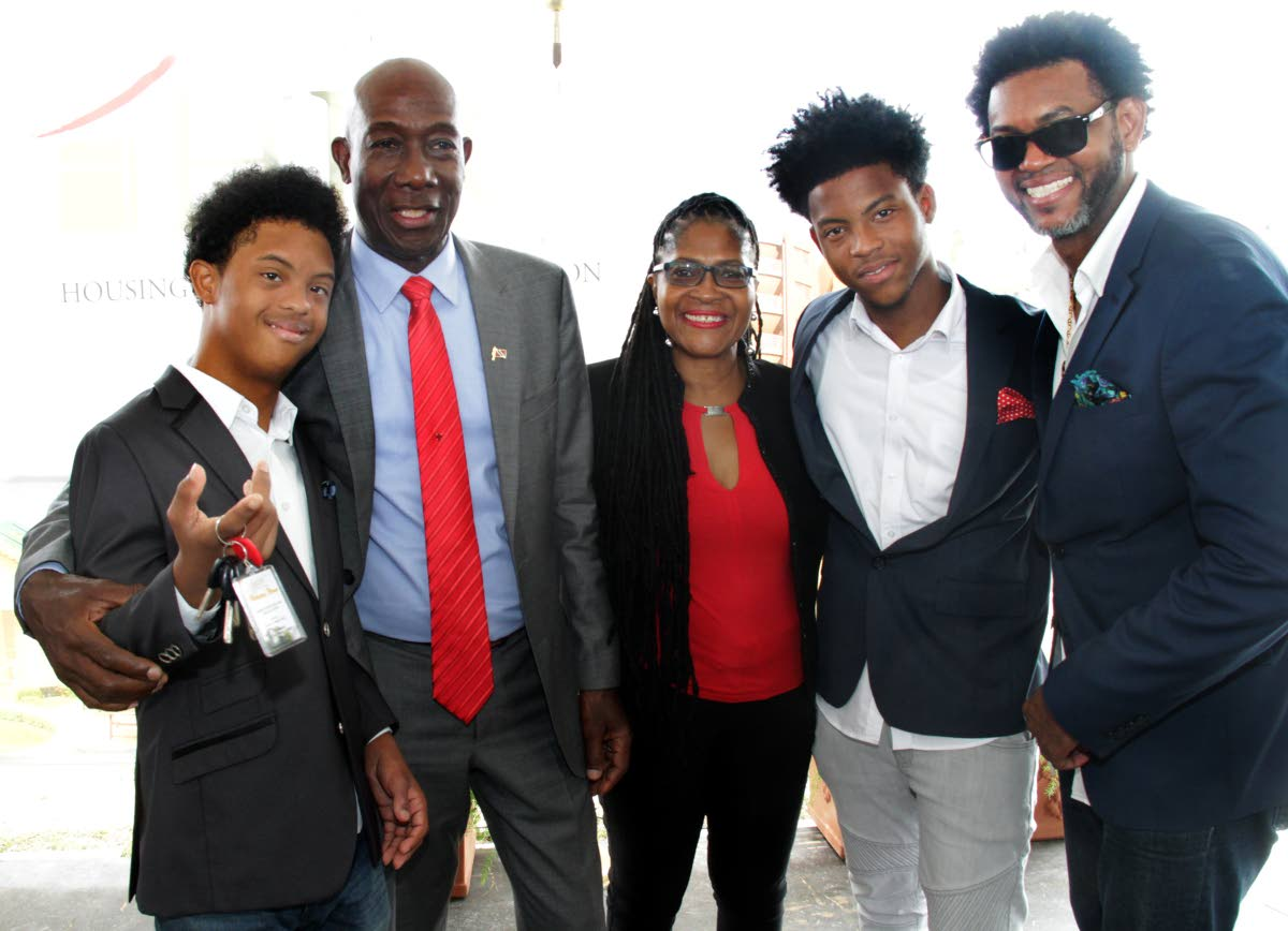 HAPPY HOME: Prime Minister Dr Keith Rowley poses with the Gulston family at a key distribuition ceremony at the Spring View housing development in Valsayn.  From left is Daniel, Dianne, Denilson and pannist Dane.
